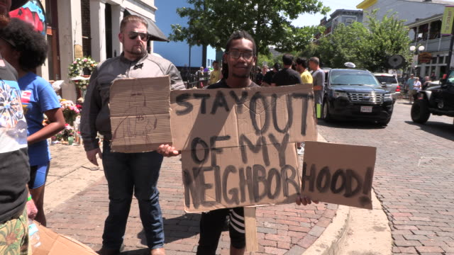 """dayton, ohio, usa: a protester holds a sign reading, """"stay out of my neighborhood,"""" as protesters gather on 5th street at the site of sunday... - dayton ohio stock videos & royalty-free footage"""
