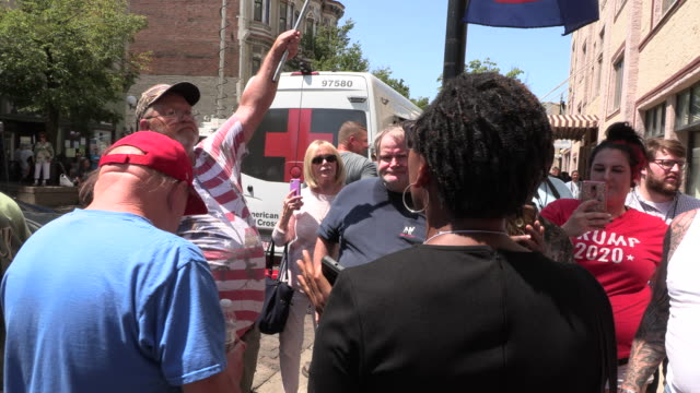 """dayton, ohio, usa: trump supporters chant, """"hell no we won't go,"""" as a protester engages with them at the site of sunday morning's mass shooting that... - ohio bildbanksvideor och videomaterial från bakom kulisserna"""