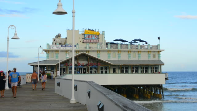vídeos de stock, filmes e b-roll de daytona beach florida famous main street pier and boardwalk pier with restaurant joes crab shack on water for tourists with boardwalk at world's most famous beach - píer