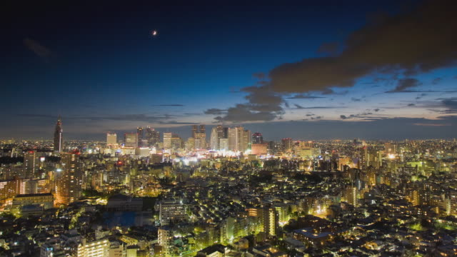 WS T/L Day-to-night transition as heavy clouds passing over Shinjuku business, shopping and entertainment district in Tokyo / Tokyo, Japan