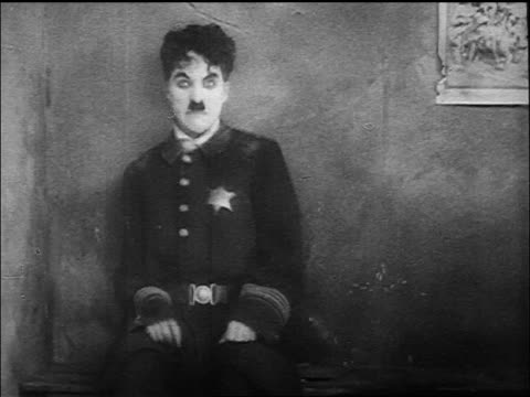 dazed policeman charlie chaplin twitches on bench + stands up pulling needle from buttocks - syringe stock videos & royalty-free footage