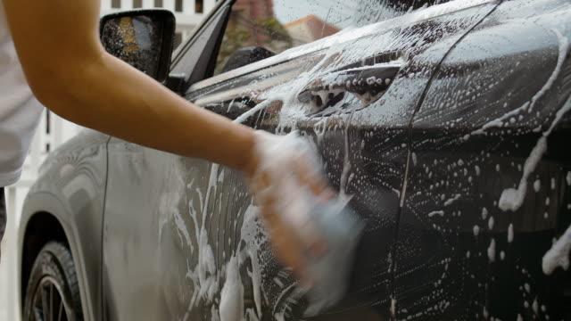 vidéos et rushes de dci 4k résolution main homme asiatique utilise l'éponge et la mousse laver voiture noire et le nettoyage de la poussière sale . - foam hand