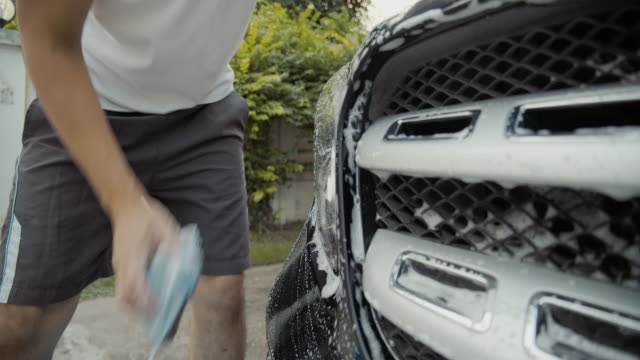 Dci 4k Resolution Asian man hand is using sponge and foam washing black car and cleaning dirty dust .