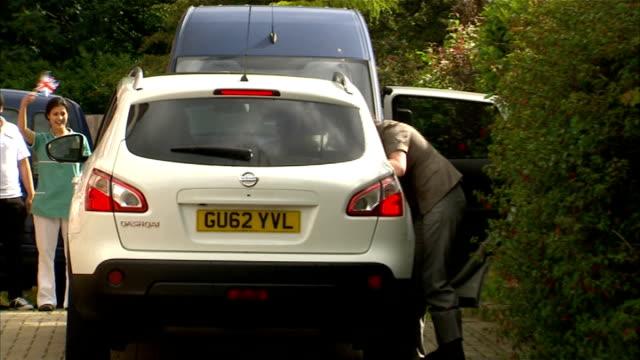 veteran bernard jordan returns to uk car arriving at care home / bernard jordan being helped out of car and being welcomed home by staff members - アロマンシェス点の映像素材/bロール