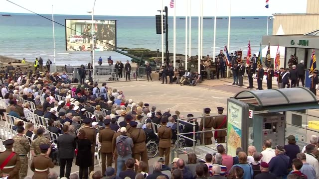 Veterans attend service in Arromanches FRANCE Normandy ArromancheslesBains Place du Six Juin 1944 EXT **Music heard SOT** People laying wreaths /...