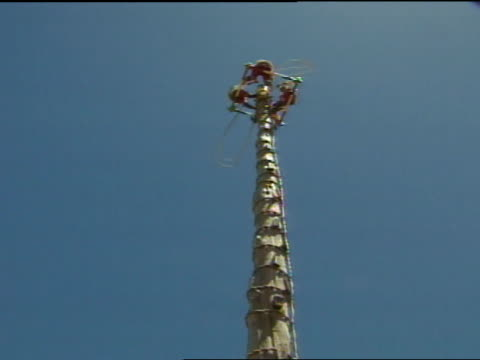 de los voladores : below indigenous totonac men in colorful traditional costumes at top of rope wrapped pole spinning platform holding ropes. - pre columbian stock videos & royalty-free footage