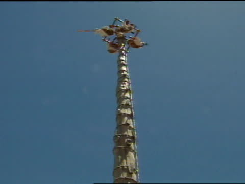de los voladores : below indigenous totonac men in colorful traditional costumes at top of rope wrapped pole, men attached by legs to ropes of... - pre columbian stock videos & royalty-free footage