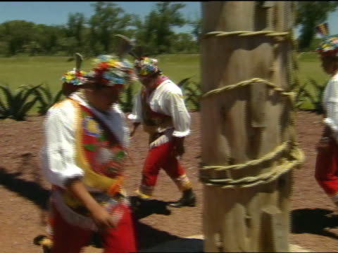 danza de los voladores indigenous totonac men in colorful traditional costumes moving around rope wrapped pole to flute music played by fifth member... - pre columbian stock videos and b-roll footage