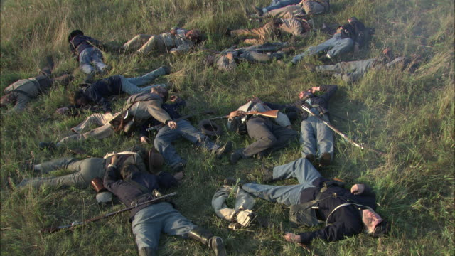 dead and and wounded union soldiers lie on a battlefield in a civil war reenactment. - battlefield stock videos & royalty-free footage