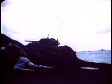 dead and wounded american soldiers tanks soldiers advancing across black sand - battle of iwo jima stock videos and b-roll footage