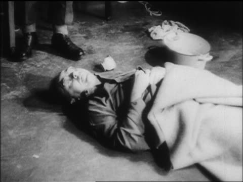 B/W 1945 dead body of Nazi Heinrich Himmler lying on floor after suicide / newsreel