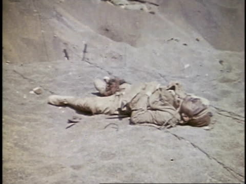 dead body on ground, soldiers carrying body on a stretcher / iwo jima - insel iwojima stock-videos und b-roll-filmmaterial