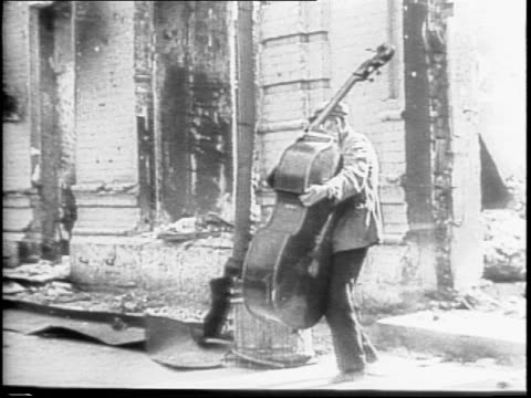 dead german soldiers on the ground / refugees carrying bags on their backs, demolished buildings in the background, a man carries his cello /... - 1942 stock videos & royalty-free footage