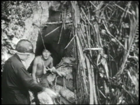 PELELIU GRAPHIC Dead Japanese soldiers face down w/ lower torso smoking VS Japanese soldiers surrendering walking down hill out of cave bunker group...