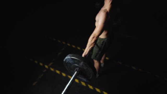夜のジムでのデッドリフティング - ウエイトトレーニング点の映像素材/bロール