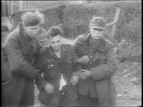 dead nazi soldiers lying on road / montage of us troops walking slowly through town, riding on tank, civilians bringing carts back into the town,... - vittima di incidente video stock e b–roll