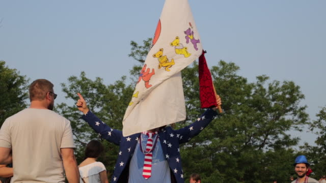 deadheads pose with another grateful dead fan dressed as uncle sam and wearing a top hat, which is red, white and blue; and waving a grateful dead... - fare video stock e b–roll
