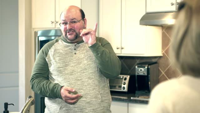 gehörlosen paar in der küche reden gebärdensprache - personen mit behinderung stock-videos und b-roll-filmmaterial