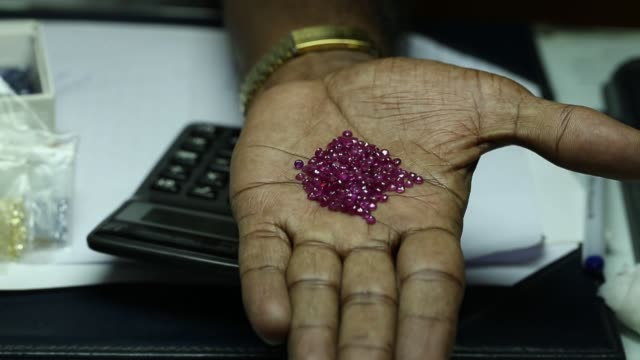 vídeos de stock e filmes b-roll de a dealer displays blue sapphires for at a gem store in ratnapura sri lanka on wednesday feb 7 amethyst gemstones sit on an open palm of a dealer... - ametista