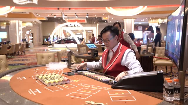 a dealer handles gaming chips on the floor of the casino at the mgm cotai casino resort developed by mgm china holdings ltd in macau china on tuesday... - casino floor stock videos & royalty-free footage