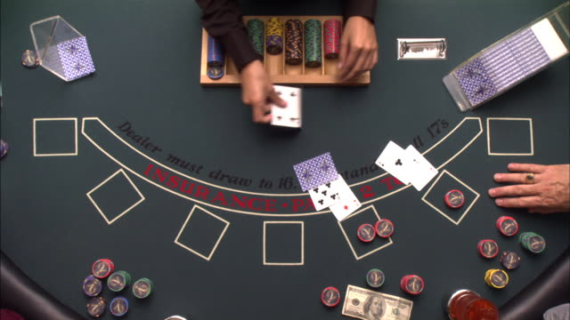 A dealer takes bets and deals cards during hands of blackjack.