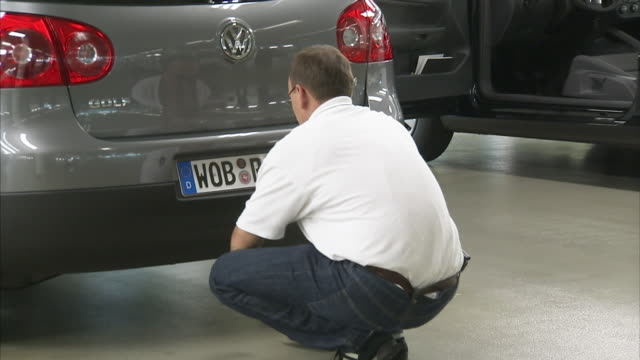 a dealer technician puts a license plate on a volkswagen golf. - volkswagen stock-videos und b-roll-filmmaterial