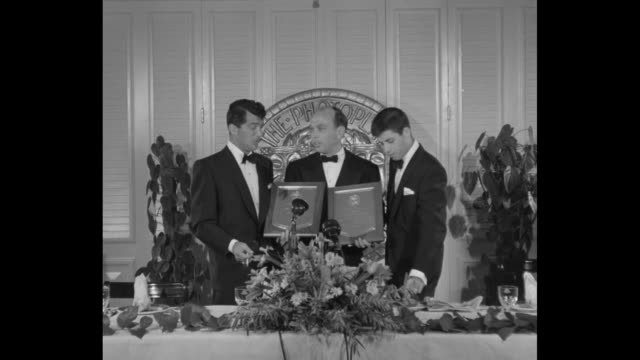 dean martin and jerry lewis hold box office award plaques in front of their faces, lower them and lewis speaks / they stand at podium with photoplay... - comedian stock videos & royalty-free footage