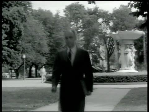 vidéos et rushes de dean of harvard regional director of us office of civil defense james m landis walking in courtyard table w/ pamphlets gas masks men examining air... - 1942
