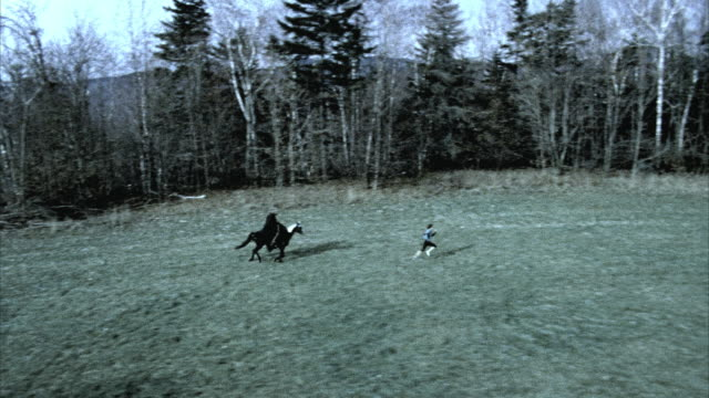 AERIAL TS  Death figure on horseback chasing woman running through meadow, Morrisville, Vermont, USA