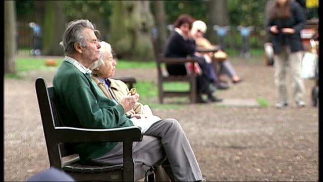 vídeos y material grabado en eventos de stock de debate over means testing pensioners benefits re-opened; kensington: ext hands of old person with plastic bag as sitting on park bench older people... - number 9