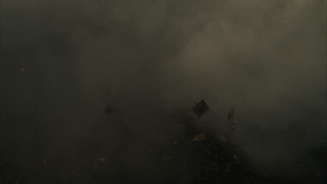 stockvideo's en b-roll-footage met debris and smoke flies through the air during a tornado. - vernieling