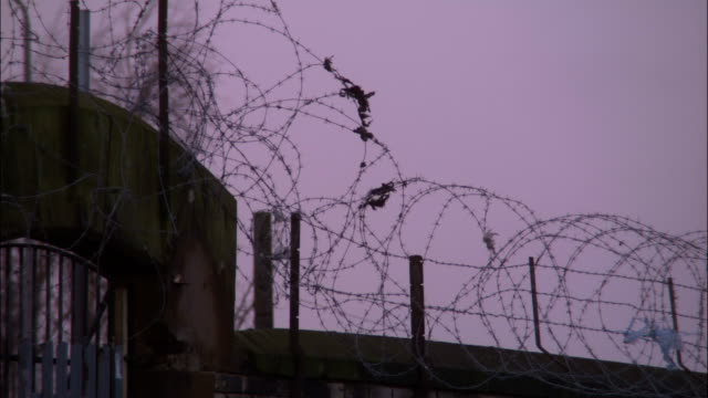 debris blows on a barbed wire fence outside a prison. - barbed wire stock videos & royalty-free footage