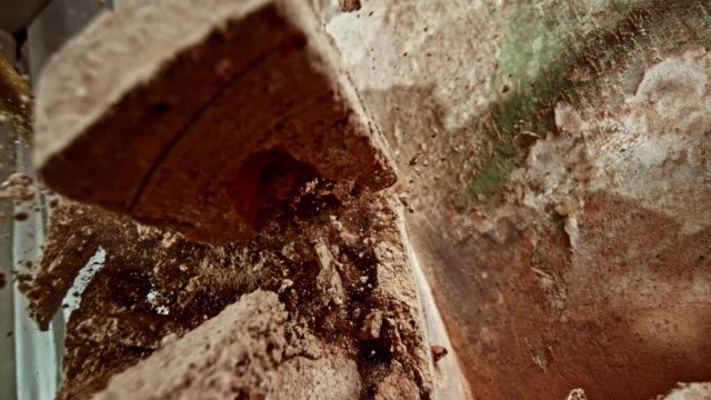 slo mo debris falling on the camera as the brick wall is struck with a sledge hammer - brick stock videos & royalty-free footage