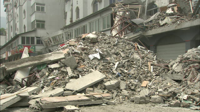 debris fills a street in front of a building destroyed in the 2008 sichuan earthquake - earthquake stock videos & royalty-free footage