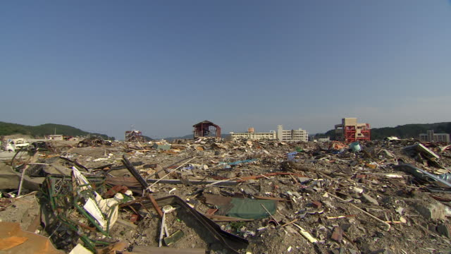 debris litters a field after a tsunami. - tsunami stock videos and b-roll footage