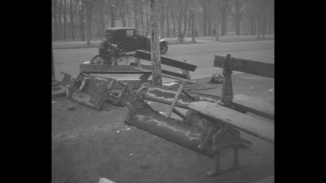 vidéos et rushes de debris on side of street including chairs table benches barricades after rioting on feb 6th / debris on street concrete metal pieces workers clean up... - 1934