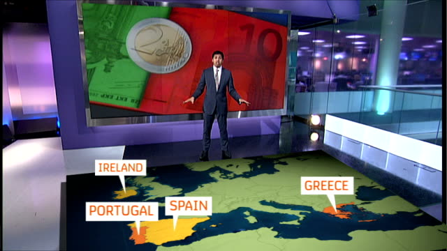 Backgrounder / British reaction Reporter to camera in front of video wall as explaining what the economic situation is in Spain