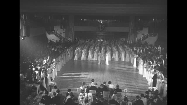 debutantes walk out onto floor during coronation ball at royal albert hall / prince george duke of kent and princess marina duchess of kent in formal... - 舞踏会点の映像素材/bロール