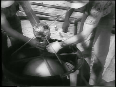 dec 6, 1957 close up 2 men put small satellite on rocket / first us attempt to put satellite in space - 1957 stock-videos und b-roll-filmmaterial