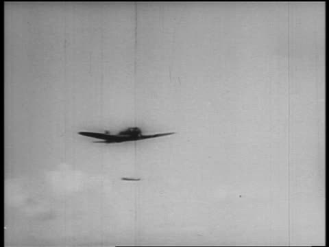 b/w dec 7 1941 shaky low angle japanese bomber dropping bomb on pearl harbor / newsreel - 真珠湾攻撃点の映像素材/bロール
