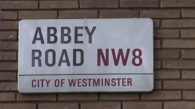 vídeos de stock e filmes b-roll de decades after the iconic beatles album the abbey road pedestrian crossing that featured on the cover is still a major tourist attraction, with... - major road