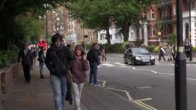 vídeos de stock, filmes e b-roll de decades after the iconic beatles album the abbey road pedestrian crossing that featured on the cover is still a major tourist attraction, with... - major road