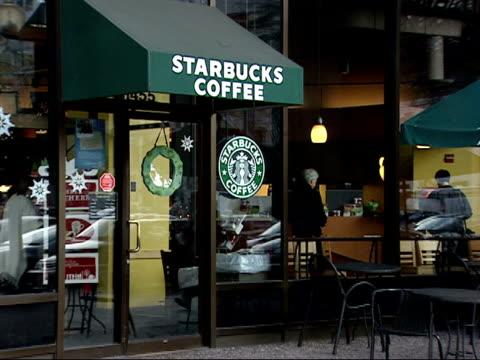 vídeos de stock, filmes e b-roll de december 12 2006 ws customer walking out of a coffee shop / washington dc united states - starbucks