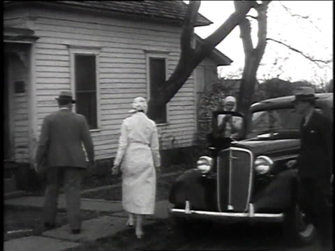 December 16 1935 WS Doctors and nurses walking away from car and into house marked with a sign that says quarantine / Snyder Oklahoma