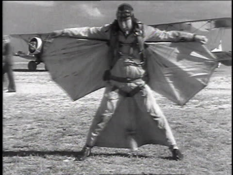stockvideo's en b-roll-footage met december 16, 1935 ws man with batwings and parachute modeling his outfit / miami, florida, united states - 1935