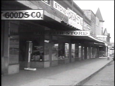 December 16 1935 WS Outside a store front a man picks up groceries that have been slid out from doorway and men standing in front of store during a...
