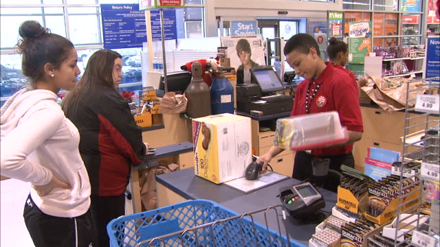 december 16 2010 ms cashier ringing up merchandise for customers in line at toy store / united states - toy store stock videos and b-roll footage