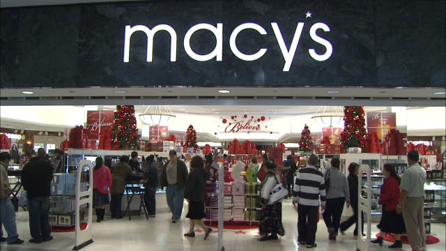 December 16 2010 WS Macy's logo hangs above entrance with customers strolling in and out of the store in an indoor mall location / United States