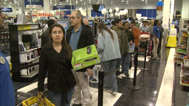 December 16 2010 PAN Shoppers waiting in line to pay for purchases and Best Buy employee directing them to available cashier / United States