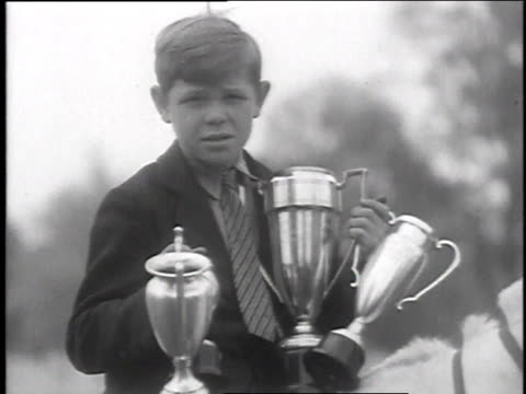 vidéos et rushes de december 18, 1935 montage boy holding trophies while sitting on horse's back, lots of blue ribbons decorating horse's bridle / wilmington, ohio, united states - award